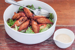 Dressing salad with fried chicken wing in white bowl Stock Images