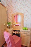 Dressing table. A wooden dressing table with a chair covered with pink textile, flowers and fruit used as decoration stock images