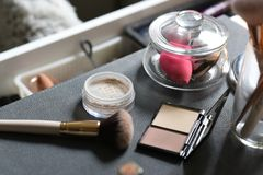 Dressing table with powder, brush, mineral foundation, sponges. Table with powder, mineral foundation, brush, makeup sponges, dressing table, makeup artist desk royalty free stock photos