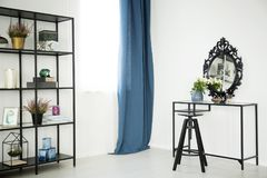 Dressing table in sophisticated interior. White flowers on dressing table with decorative mirror in sophisticated interior with blue curtain Stock Images