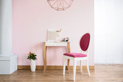 Dressing table and upholstered chair. Pink room with column, dressing table and upholstered chair stock images