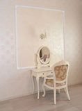 Dressing table and white chair in a hotel room Stock Photo