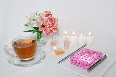 Dressing table with women`s accessories. Image of a pink gift box with a bouquet of Alstroemeria flowers, candles, perfume, tea cu. Ps, and notepad. With an royalty free stock photography