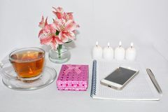 Dressing table with women`s accessories. Image of a pink gift box with a bouquet of Alstroemeria flowers, romantic candles. Perfume, tea cups, notepad and cell stock photos