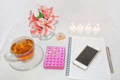 Dressing table with women`s accessories. Image of a pink gift box with a bouquet of Alstroemeria flowers, romantic candles. Perfume, tea cups, notepad and cell royalty free stock image
