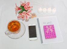 Dressing table with women`s accessories. Image of a pink gift box with a bouquet of Alstroemeria flowers, romantic candles. Perfume, tea cups, notepad and cell royalty free stock photo
