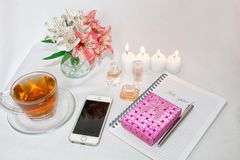 Dressing table with women`s accessories. Image of a pink gift box with a bouquet of Alstroemeria flowers, romantic candles, perfum. E, tea cups, notepad and cell stock images