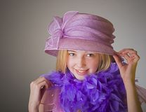 Dressing up. Little girl with pink hat and purple boa stock photography