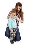Dressing up the toddler. Young caucasian mother dressing up her little boy, isolated on white background Royalty Free Stock Photography