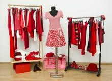 Dressinggarderoben med rött och vit beklär ordnat på hängare och en dräkt på en skyltdocka. Arkivbilder