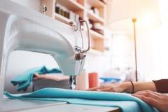 Dressmaker молодой женщины работая на швейной машине внутри шьет выставочный зал Белошвейка работая с тканью в мастерской стоковое фото