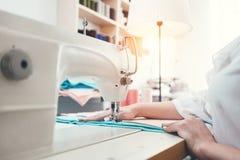 Dressmaker молодой женщины работая на швейной машине внутри шьет выставочный зал Белошвейка работая с тканью в мастерской стоковое фото rf