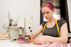 Dressmaker. With sewing machine in her studio stock image
