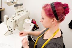 Dressmaker. With sewing machine in her studio royalty free stock image