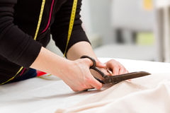 Dressmaker cutting fabric with scissors Royalty Free Stock Images