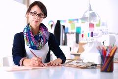 Dressmaker designing clothes pattern on paper Stock Images
