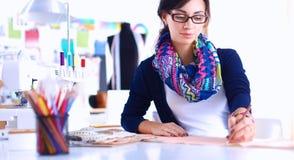 Dressmaker designing clothes pattern on paper Stock Image