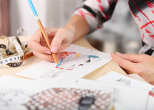 Dressmaker is drawing a fashion sketch. Close up of the hands royalty free stock photo