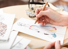 Dressmaker is drawing a fashion sketch. Close up of the hands royalty free stock image