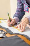 Dressmaker drawing tailor pattern on the table Stock Image