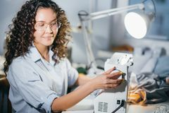Dressmaker is fixing white sewing machine in workshop Stock Photo