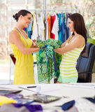 Dressmaker hand over dress to client Royalty Free Stock Photography