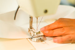 Dressmaker job, hands sewing with a sewing machine. White fabric and dark thread.  Stock Photo