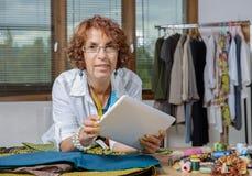 Dressmaker look at a digital tablet Stock Photography