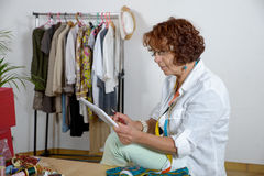 Dressmaker look at a digital tablet Royalty Free Stock Image