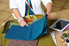 Dressmaker look at a digital tablet in his workshop Royalty Free Stock Photos