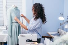Dressmaker measuring breast of garmenr on dummy to make recesses. In room stock photos