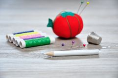 A dressmaker pencil with an out of focus pin cushion shaped as a red tomato, rolls of thread and a thimble. On a wooden background stock photos