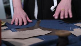 Dressmaker`s hands laying out cut pattern on table. Close-up of seamstress`s hands working with cut patterns on worktable in sewing atelier. Skillful female stock video footage