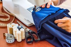 Dressmaker or seamstress works using sewing machine. Reels, scissors, tape measure and a sewing machine. Workplace stock photography