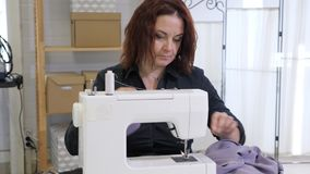 Seamstress woman is working on sewing machine in tailoring workshop business. stock footage