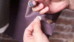 Dressmaker sews a button on jacket Stock Photos