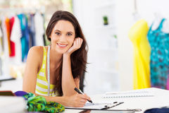 Dressmaker sketching. Attractive young female dressmaker sketching in studio Stock Photos