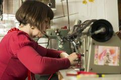 Dressmaker Stitiching Fabric Through Sewing Machine Royalty Free Stock Photos
