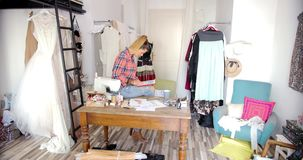 Dressmaker with tablet in parlour stock video