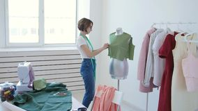 Dressmaker, tailor and fashion concept - Female clothing designer at workplace in studio stock video footage
