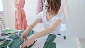 Dressmaker, tailor and fashion concept - Female clothing designer at workplace in studio stock footage
