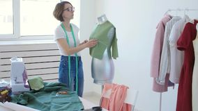 Dressmaker, tailor and fashion concept - Female clothing designer at workplace in studio stock video