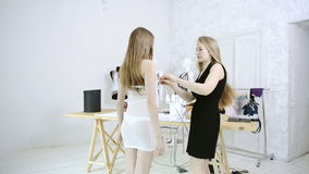 Dressmaker takes measurements woman for sewing clothes in studio. Seamstress in black dress with long white straight hair holding meter, measures client in stock video