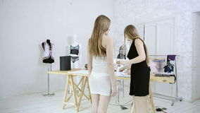 Dressmaker takes measurements with woman for sewing dresses in studio. Seamstress in black dress with long white straight hair holding meter, measures client stock video footage