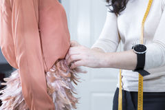 Dressmaker tweaking a dress Stock Photo