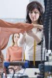 Dressmaker tweaking a sleeve. Dressmaker is tweaking the sleeve of the the dress of a female customer at her sewing atelier - focus on the dressmaker right eye stock photo
