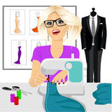 Dressmaker woman using sewing machine. Attractive young blonde fashion designer dressmaker woman using sewing machine to sew a turquoise tissue Royalty Free Stock Photo