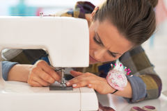 Dressmaker woman working with sewing machine Stock Images