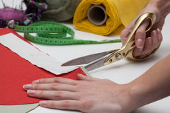 Dressmaker at work. Dressmaker with scissors cutting material for cloth royalty free stock image