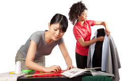 Dressmaker at Work. Two young women dressmaker at work royalty free stock images